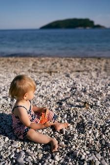 ドレスを着た少女が海側の小石のビーチに座っています。