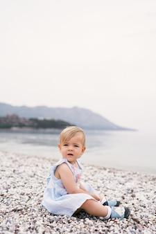 ドレスを着た少女が海沿いの小石のビーチに座っています