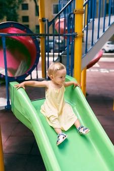 드레스를 입은 어린 소녀가 놀이터에서 미끄럼틀을 미끄러져 내려옵니다