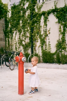 드레스를 입은 어린 소녀가 건물 앞 빨간 소화전 근처에 서 있다
