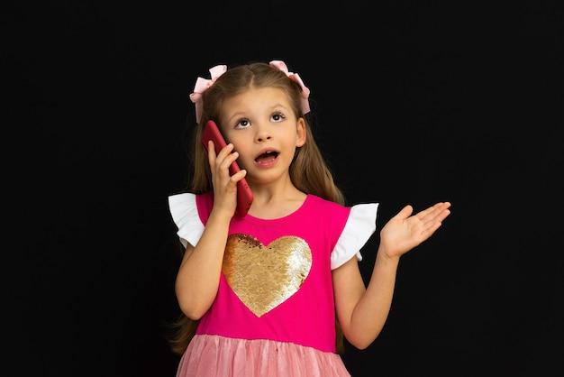 Маленькая девочка в платье разговаривает по телефону.