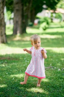 ドレスを着た少女が緑の芝生の上を裸足で歩く