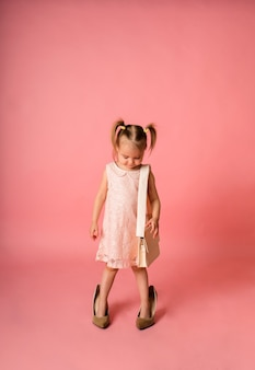お祝いのドレスと母親の靴を履き、バッグを持った少女は、テキストの場所があるピンクの表面を見下ろします