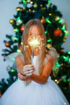 Маленькая девочка в праздничном платье с бенгальскими огнями на фоне елки