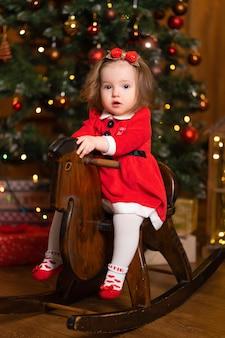 Маленькая девочка в праздничном платье на деревянной лошадке-качалке
