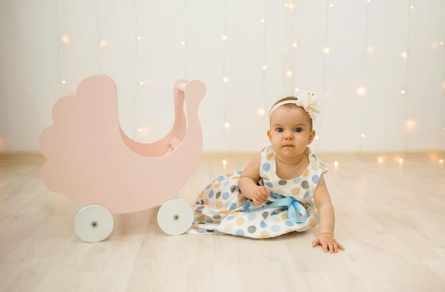Маленькая девочка в праздничном платье играет с деревянной коляской на белой стене с гирляндой