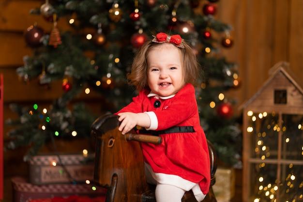 Маленькая девочка в праздничном красном платье на деревянных качелях-лошадках