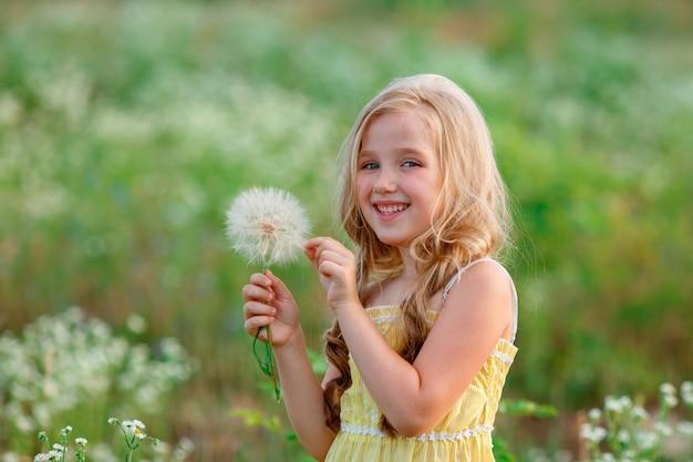 Маленькая девочка в поле с одуванчиком гуляет летом