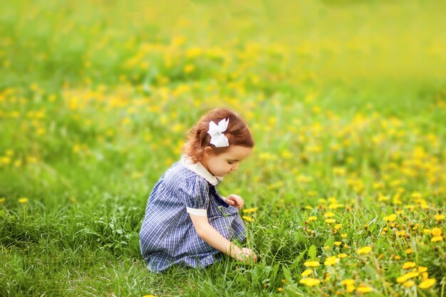 Маленькая девочка в цветущем поле с одуванчиками. ретро винтажная мода.