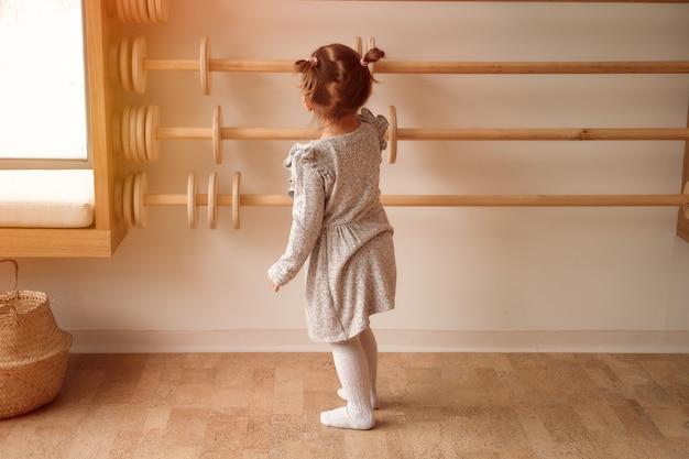 회색 드레스를 입은 어린 소녀가 어린이 방에서 나무 주판을 가지고 노는 나무를 세는 법을 배웁니다.
