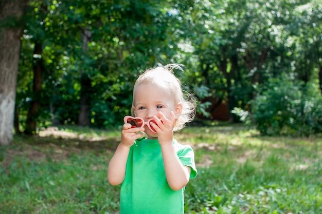 녹색 티셔츠와 분홍색 하트 모양의 선글라스를 쓴 어린 소녀가 여름에 공원을 산책합니다. 고품질 사진