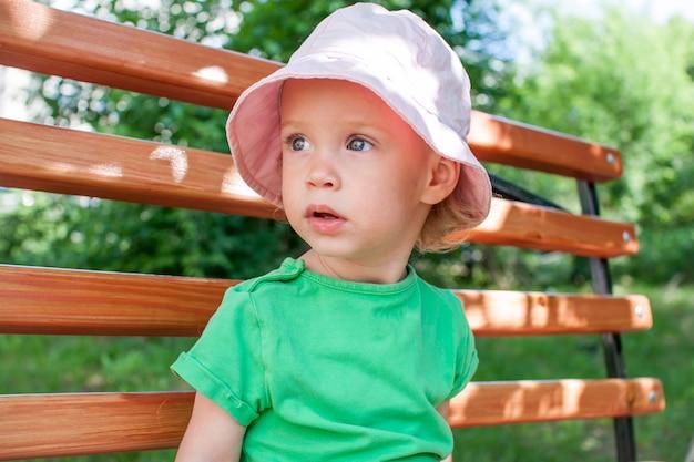 녹색 티셔츠와 분홍색 파나마를 입은 어린 소녀가 여름에 공원을 산책합니다