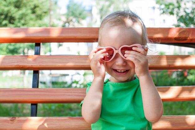녹색 티셔츠와 분홍색 하트 모양의 선글라스를 쓴 어린 소녀가 여름에 공원을 산책합니다