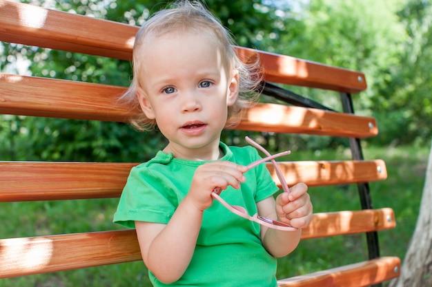 녹색 티셔츠와 분홍색 하트 모양의 선글라스를 쓴 어린 소녀가 여름에 공원을 산책합니다 프리미엄 사진