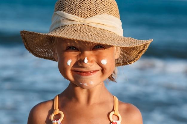 青い海を背景に帽子をかぶった少女