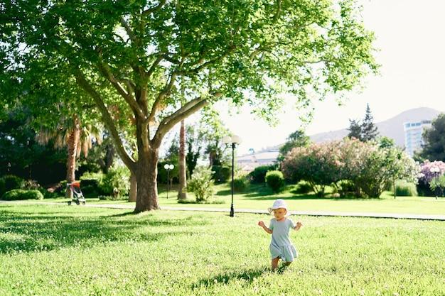 帽子をかぶった少女は、木々や花の茂みを背景に緑の芝生の上を歩きます