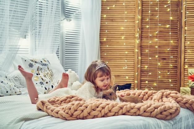 明るい色と縁のニットドレスの少女がぶら下がっているベッドにあります。