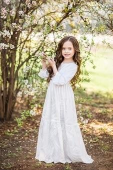 春の庭で長い白いドレスを着た少女。花の咲く木の近くの子供