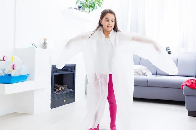 의료복을 입은 어린 소녀가 의사에게 꿈을 꾸고 집에서 놀다