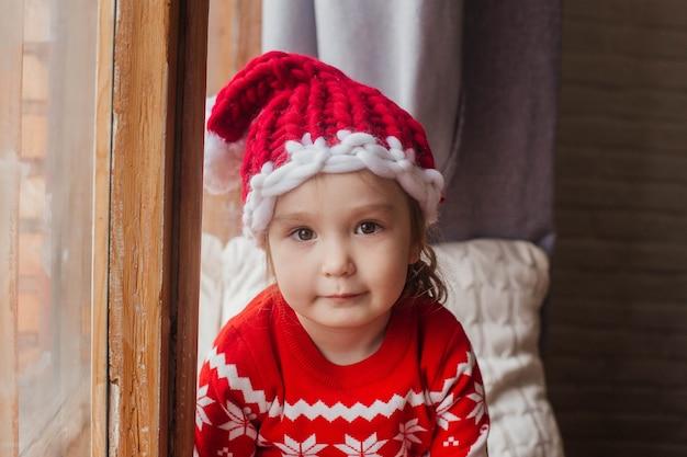 창가에 앉아 새 해 스웨터와 모자 미소에 어린 소녀.