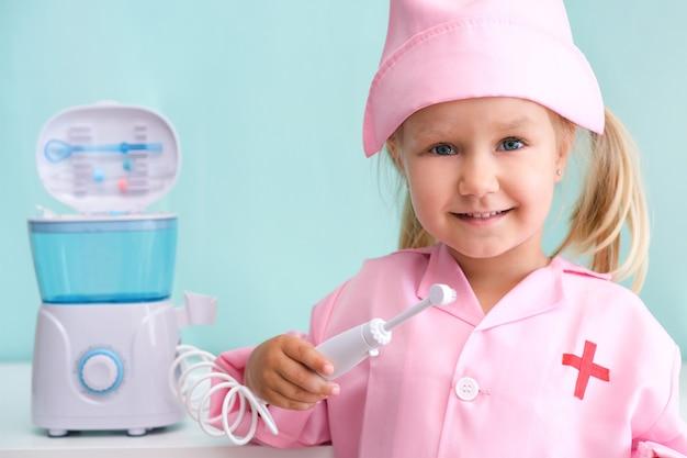 ナースガウンを着た少女は、灌漑器を使って歯を磨きます。女の子は、ウォーターピックからの水の流れで歯を磨いています。