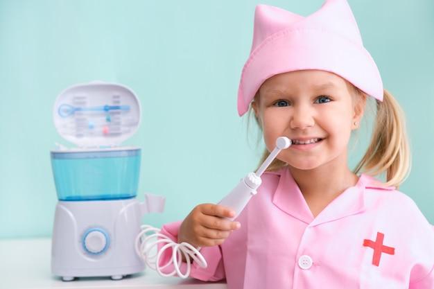 Маленькая девочка в халате медсестры чистит зубы с помощью ирригатора. девушка чистит зубы струей воды из ирригатора.