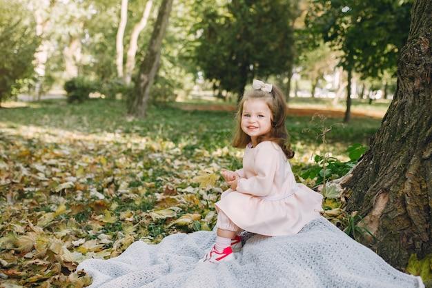 Маленькая девочка в парке в розовом платье играет