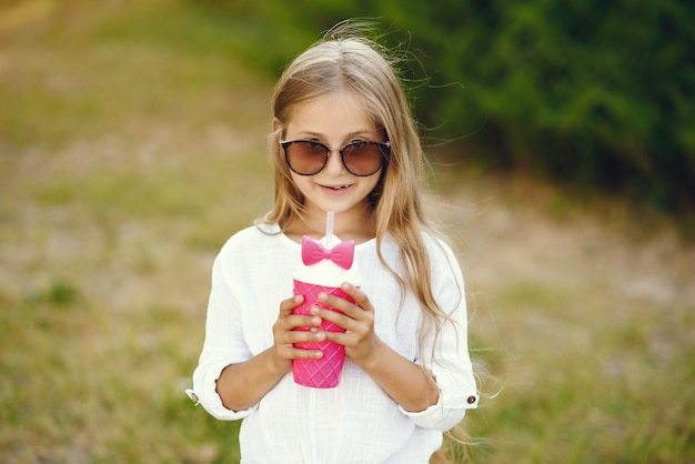 Маленькая девочка в парке стоит с розовой чашкой