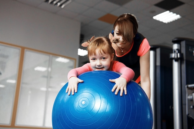 Маленькая девочка в розовой блузке занимается с мамой на фитболе, мама помогает дочери прыгать на фитболе в тренажерном зале, счастливая девочка занимается на фитболе
