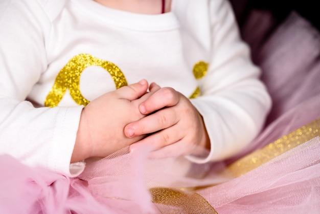 Маленькая девочка в розовом платье со сложенными руками.