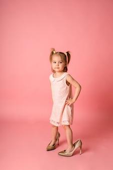 Маленькая девочка в розовом кружевном платье и туфлях ее матери стоит на розовой поверхности с местом для текста