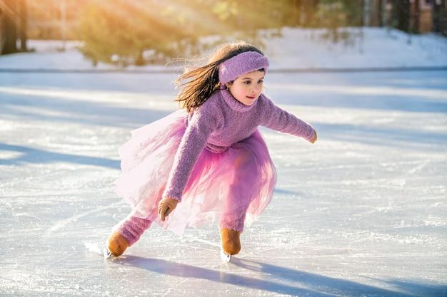 Маленькая девочка в розовом свитере и пышной юбке катается солнечным зимним днем на открытом катке в парке