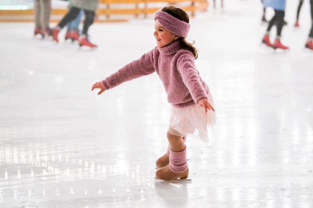 Маленькая девочка в розовом свитере катается зимним вечером на открытом катке, освещенном гирляндами