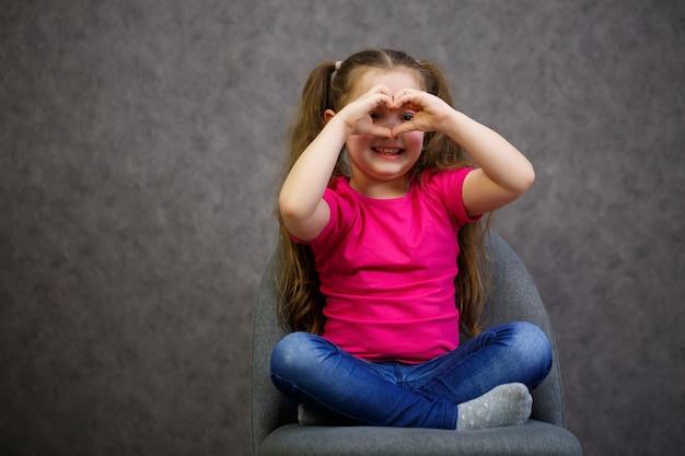 Маленькая девочка в розовой футболке сидит на сером стуле. эмоциональное фото ребенка Premium Фотографии