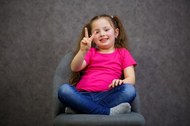 Маленькая девочка в розовой футболке сидит на сером стуле. эмоциональное фото ребенка