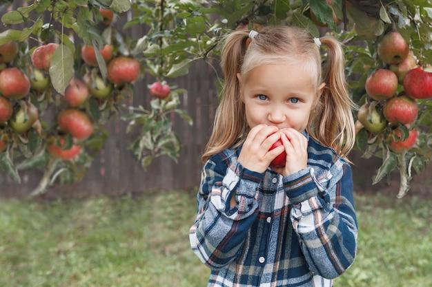 격자 무늬 셔츠를 입은 어린 소녀는 정원에서 사과를 먹고 카메라를 본다
