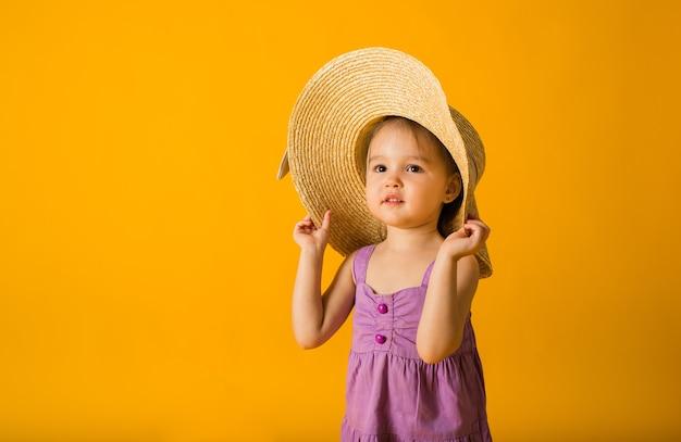 Маленькая девочка в фиолетовом платье и соломенной шляпе на желтой поверхности с пространством для текста