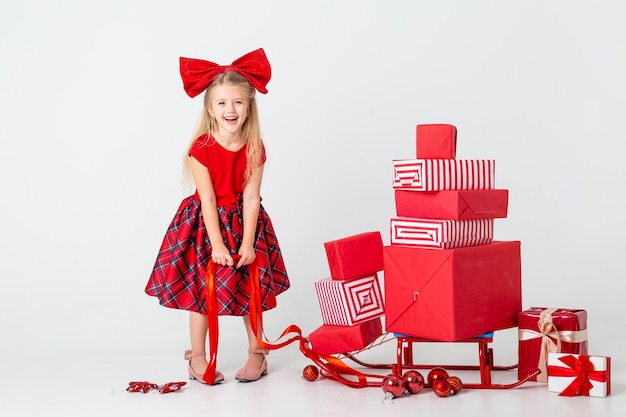 빨간 드레스를 입은 어린 소녀가 새해 선물로 썰매를 굴립니다. 흰색 배경, 텍스트를위한 공간입니다. 크리스마스의 개념
