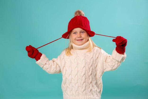 Маленькая девочка в красной вязаной шапке, варежках и белом свитере улыбается на синей стене