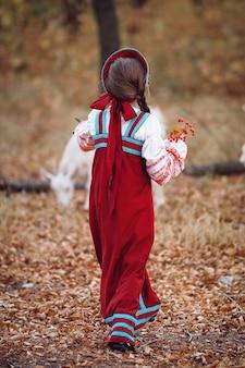 Маленькая девочка в красном сарафане вид сзади