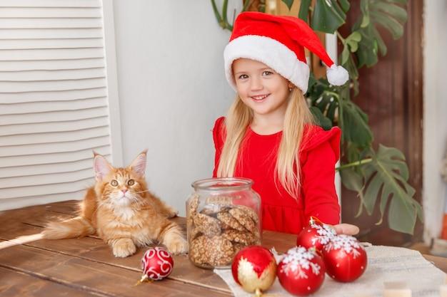 キッチンで猫とサンタの帽子をかぶった少女