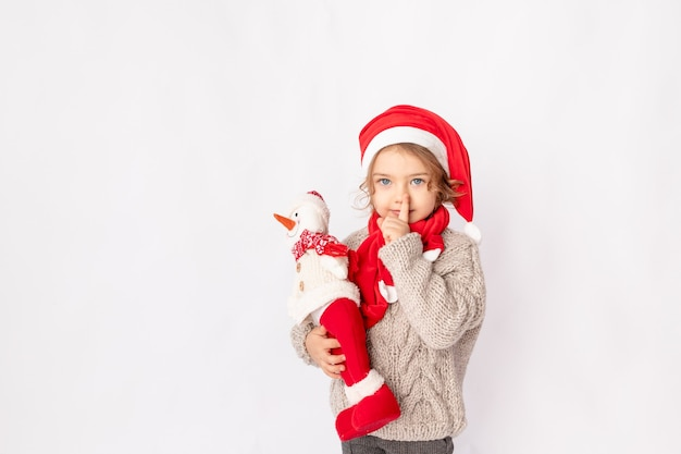 Маленькая девочка в шляпе санты со снеговиком на белом фоне, место для текста