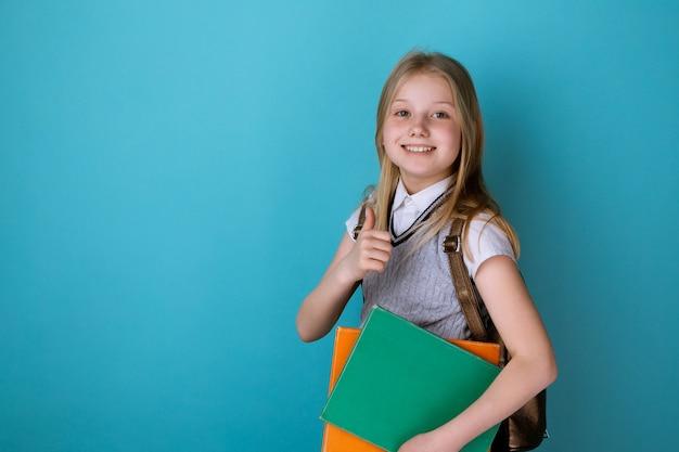 Маленькая девочка в школьном платье стоя изолировала синий фон.
