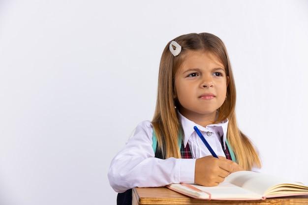 빈 공간이 흰 벽에 테이블에 앉아 학교 유니폼에 어린 소녀. 여학생은 숙제를하고 신중하게 멀리 바라보고 있습니다. 교육 개념.