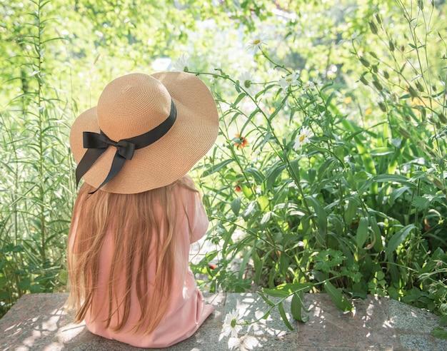 꽃으로 둘러싸인 밀짚 모자를 쓴 어린 소녀