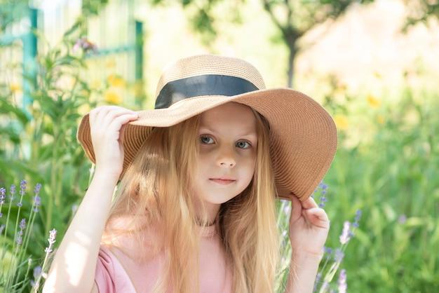 라벤더 꽃으로 둘러싸인 밀짚 모자를 쓴 어린 소녀