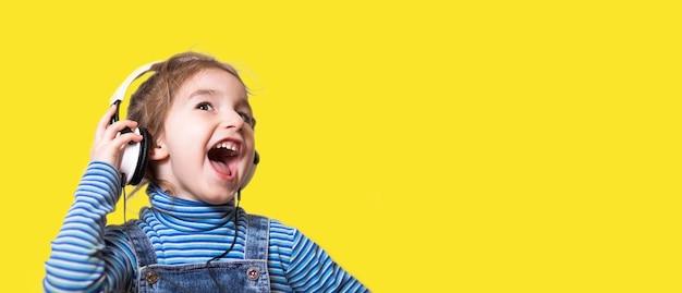 縞模様の青いタートルネックの少女は、白いヘッドホンで音楽を聴き、口を開けて大声で歌います。楽しい、叫ぶ、子供の感情。