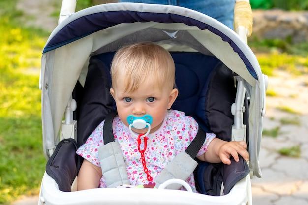 Маленькая девочка в коляске с соской во рту