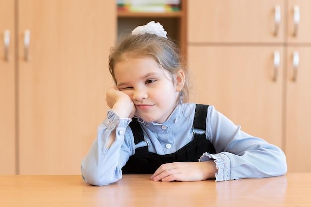 Маленькая девочка в сарафане скучает по столу. для любых целей.