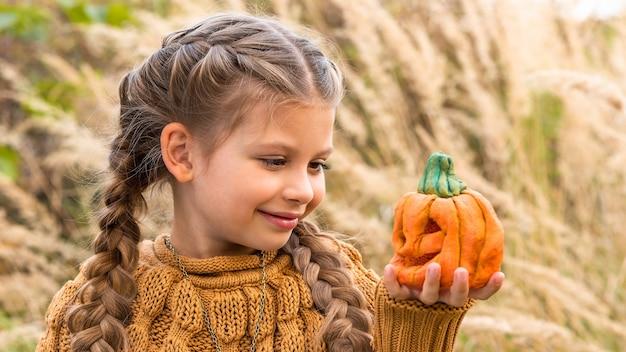 Маленькая девочка в свитере смотрит на искусственную тыкву на хэллоуин.